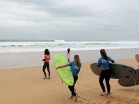 Alumnas en la orilla con las tablas de surf