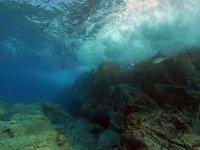 Perspectiva acuática de las olas rompiendo contra las rocas