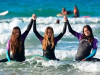 Surfers in Cantabria holding hands