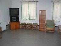 sala con television y sillas en las paredes