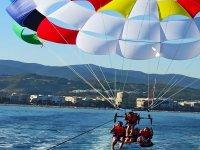 Familia volando en parasailing