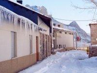 Casa con hielo en el techo y nieve en el suelo