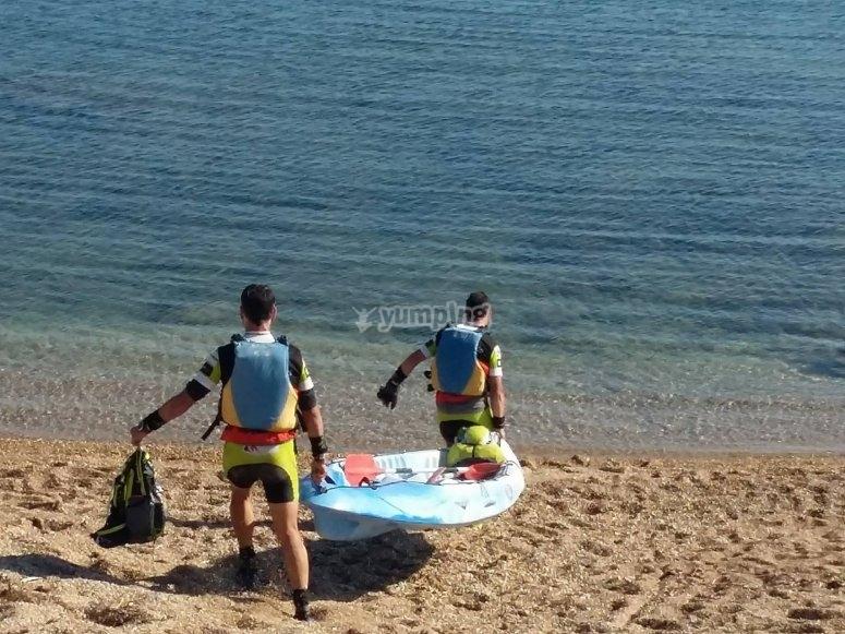 Chicos llevando el kayak al agua