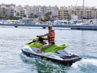 Young man leaving the port on a jet ski