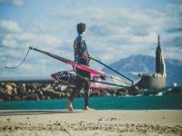 在沙滩上携带风帆冲浪板