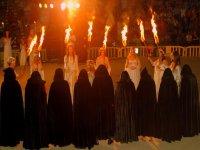 espectaculo de magia con personas vestidas de negro y otras de blanco