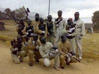 grupo de chicos con monos cascos y pistolas de paintball