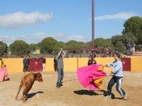 hombres en una plaza de toros haciendo un recorte a la vaquilla