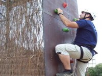 hombre escalando por un rocodromo vertical