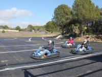 tres personas en un circuito de karting