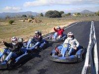 varios chicos saludando a punto de comenzar una carrera de karting
