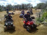 chicos conduciendo unos miniquads en un terreno de arena