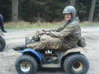 hombre lleno de barro en un quad