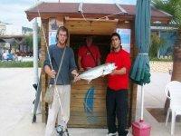 dos hombres ensenando un pez