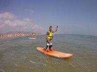 De rodillas sobre la tabla de paddle surf