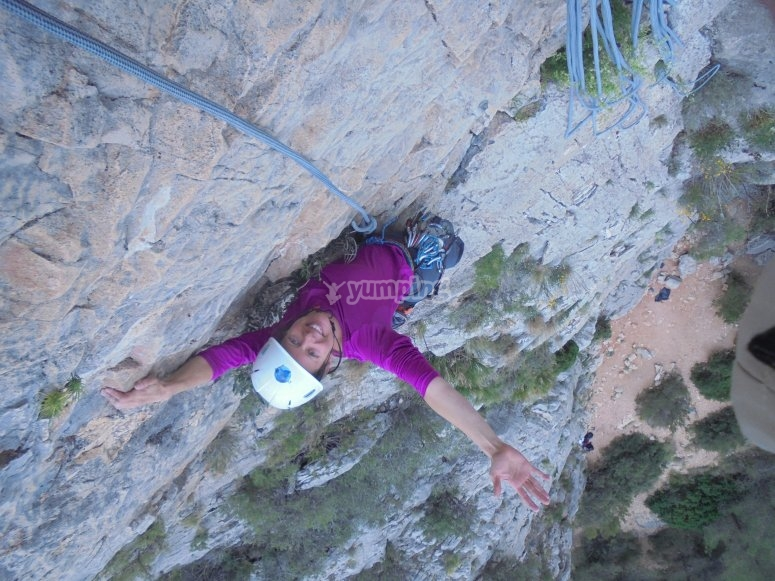 chica que saluda en la escalada