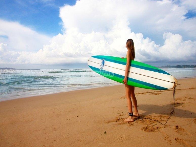 chica coge una tabla de surf en la playa