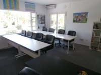 sillas negras junto a unas mesas blancas