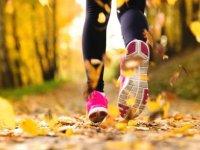 los pies de una chica levantando hojas