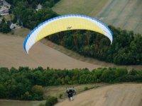 一个满是树木的景观上的动力伞飞行