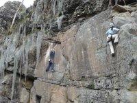 dos hombres escalando por una pared