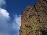 hombre escalando la cima de una montana