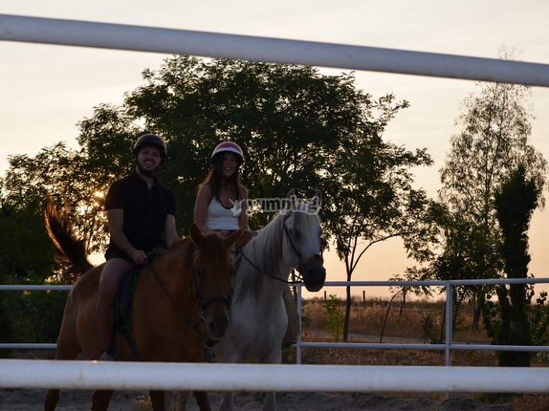 Pareja aprendiendo equitacion