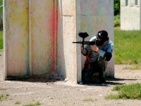 boy behind a wall while playing paintball