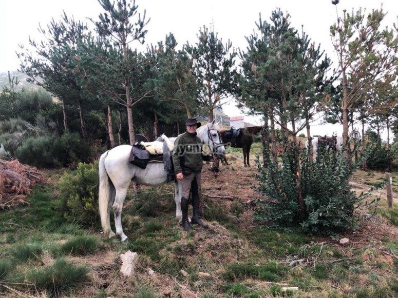 Posando con el caballo ante los arboles