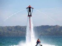 hombre de espaldas practicando flyboard con chorros de agua bajo sus pies y manos