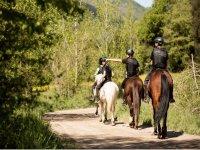 Tres personas de paseo en caballo