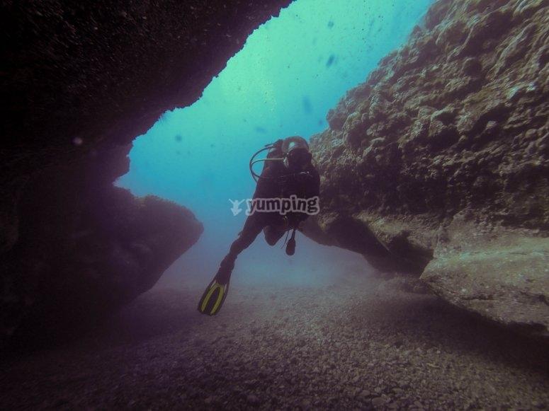Diver among rocks at the sea bottom