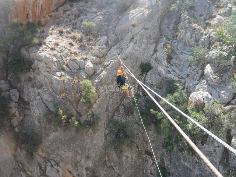Sliding in zip line through the Barranco del Ciervo