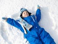 niño haciendo ángel de nieve