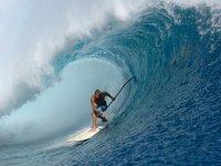 hombre debajo de una ola practicando paddle surf