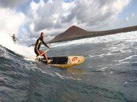 hombres haciendo paddle surf en fuertes olas