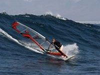 hombre de lado cogiendo una ola mientras practica windsurf