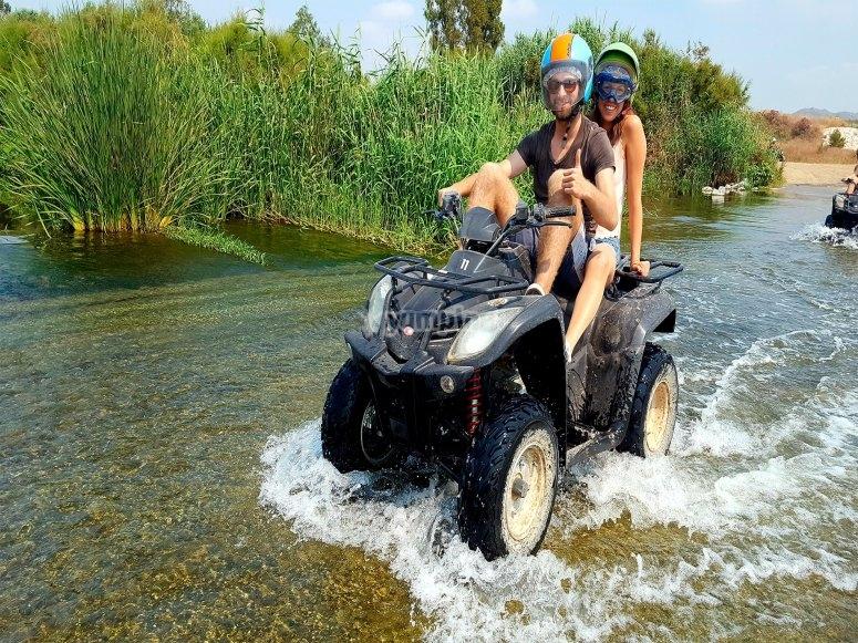 Atravesando un rio en pareja y subidos a un quad