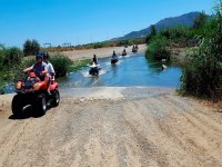 Cruzando el rio subidos a un quad