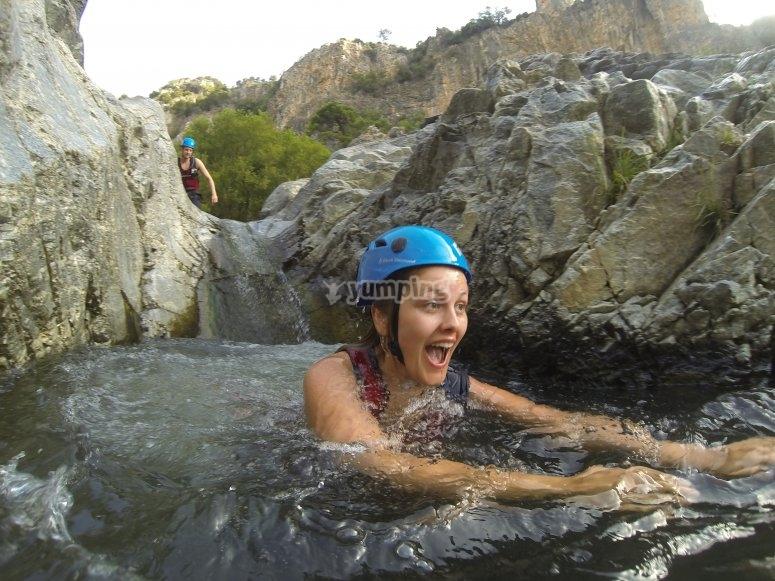 Chica equipada con casco en la ruta de barranquismo