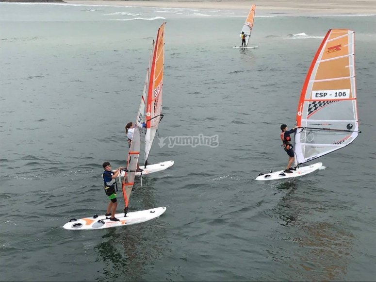 Group of children navigating on the windsurf board