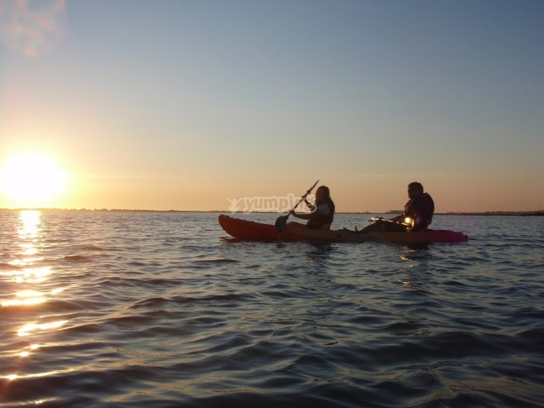 Kayaking in pairs with the sun falling