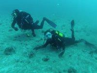 dos buceadores tocando el fondo marino