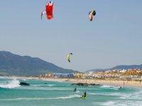 varias personas practicando kitesurf en tarifa
