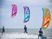 Chicos volando sus cometas mientras practican kitesurf