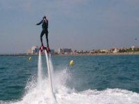 Boy on his back practicing flyboard in the air