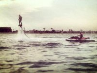 Boy practicing flyboard while another man drives a watercraft