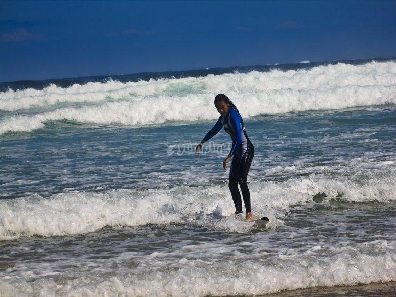 Chica aprendiendo a surfear en orilla