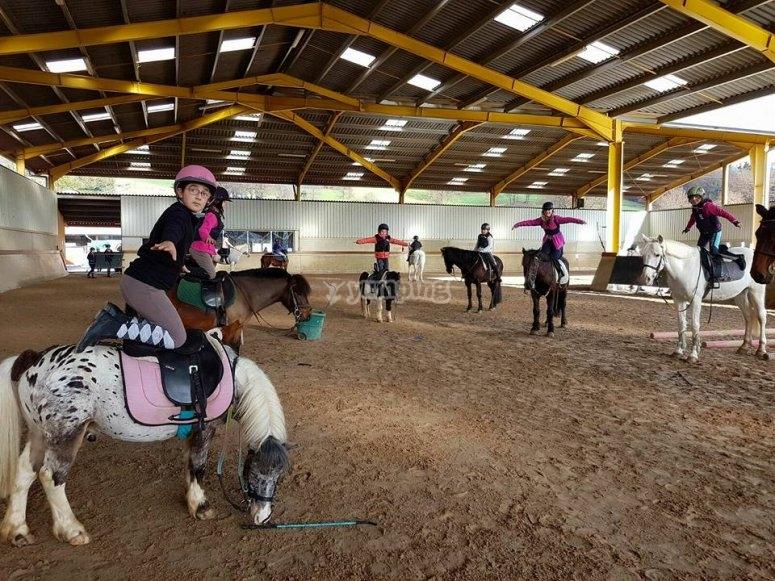 Niños aprendiendo a montar en poni