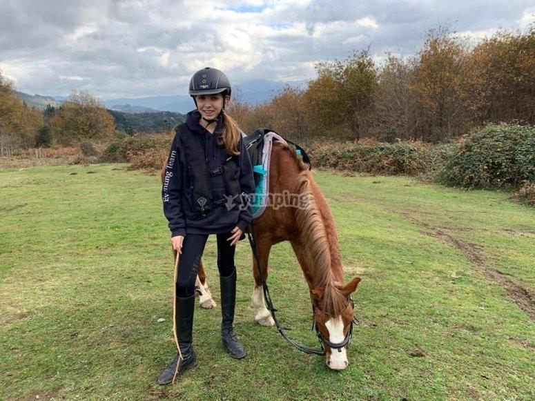Niña con caballo en el prado